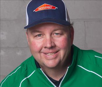 man in green jacket and baseball hat smiling