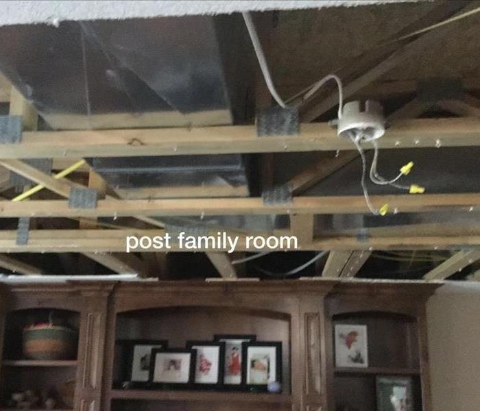 a living room without the sheetrock on the ceiling due to mold damage in attic